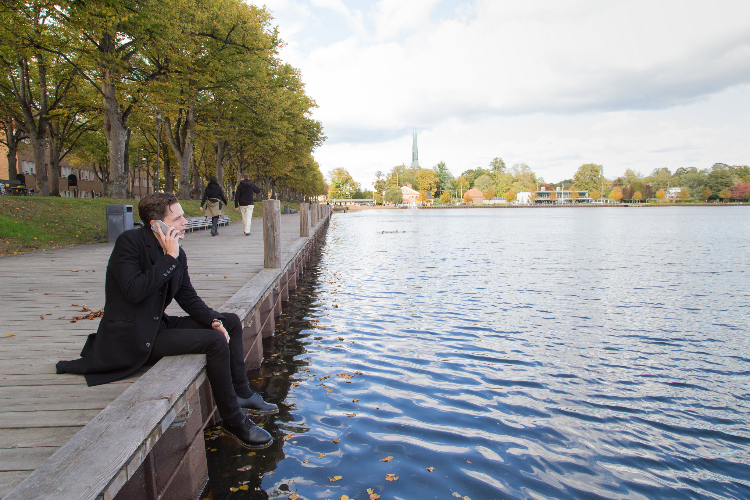 Student talking on the phone by the lake in Växjö
